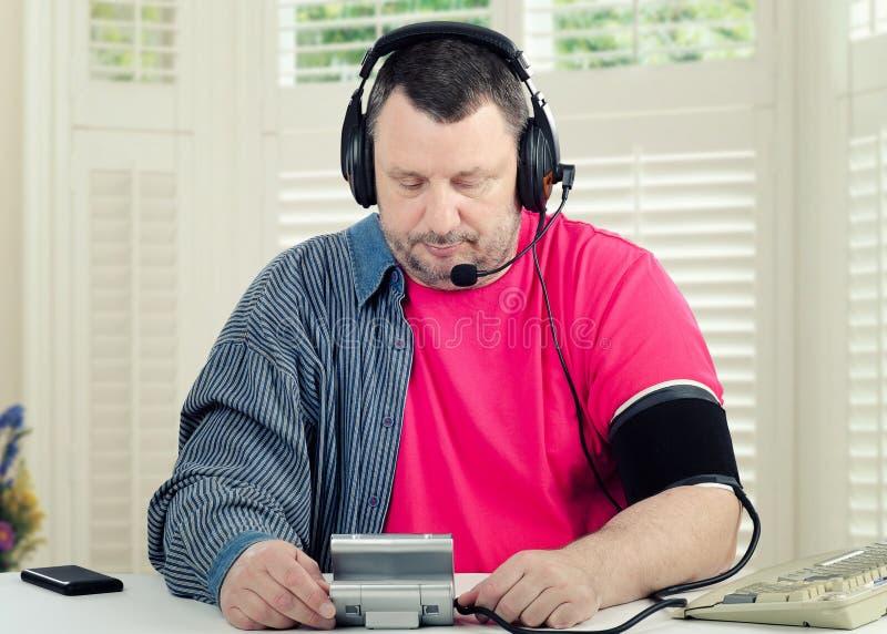 Telemedicinepatient i hörlurar med mikrofon som mäter blodtryck arkivfoton