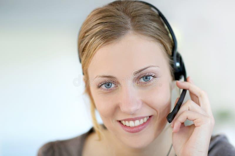 Teleoperator för ung kvinna med hörlurar med mikrofon arkivbild