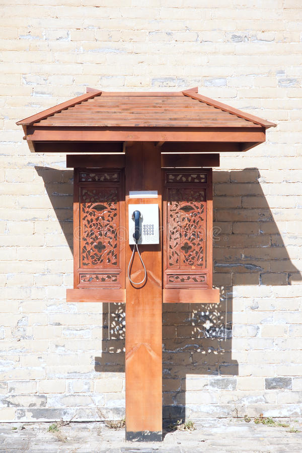 Telephone booth. The close-up of a telephone booth stand in front of brick wall royalty free stock photography