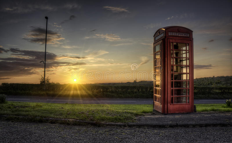 Telephone Box. A sunset behind an old fashioned english telephone box royalty free stock images
