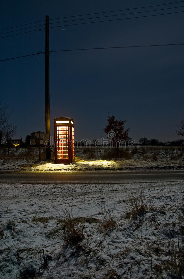 Telephone Box at night. This is a long exposure photo of a British telephone box taken at night time during winter and snow covered ground. The location is in royalty free stock photo