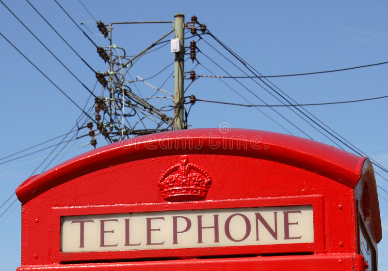 Telephone Call. A red telephone kiosk with telecommunication infrastructure behind royalty free stock photos