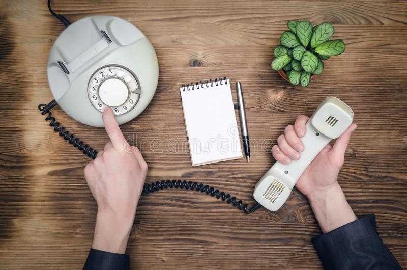 Contact us. Telephone in male businessman hands and notebook with copy space on office table. Contact us. Business conversation stock image