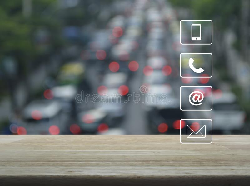 Business customer service and support concept. Telephone, mobile phone, www and email buttons on wooden table  over blur of rush hour with cars and road in city stock image