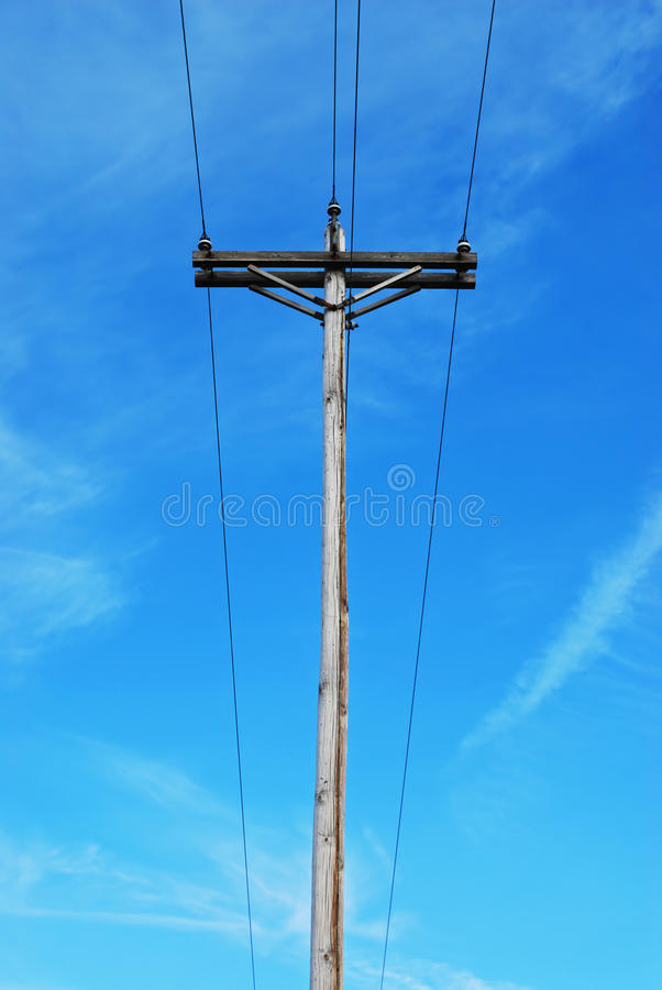 Telephone pole. Old telephone pole against blue sky stock image