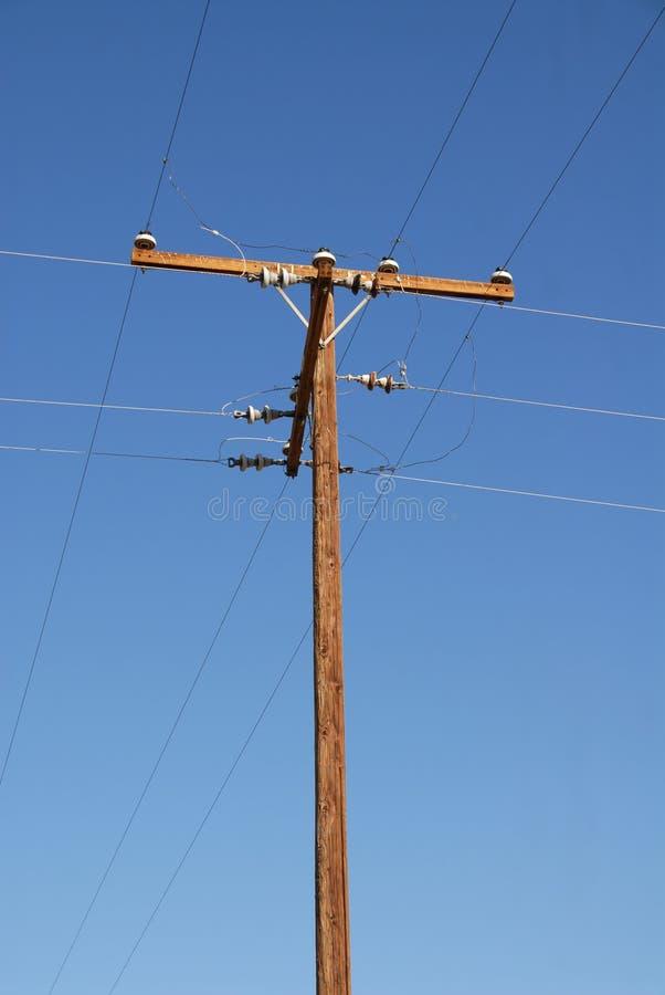 Telephone pole. An old telephone pole against a blue sky stock image