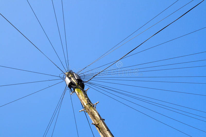 Telephone pole. Telephone pole with lots of lines and a blue sky stock photography