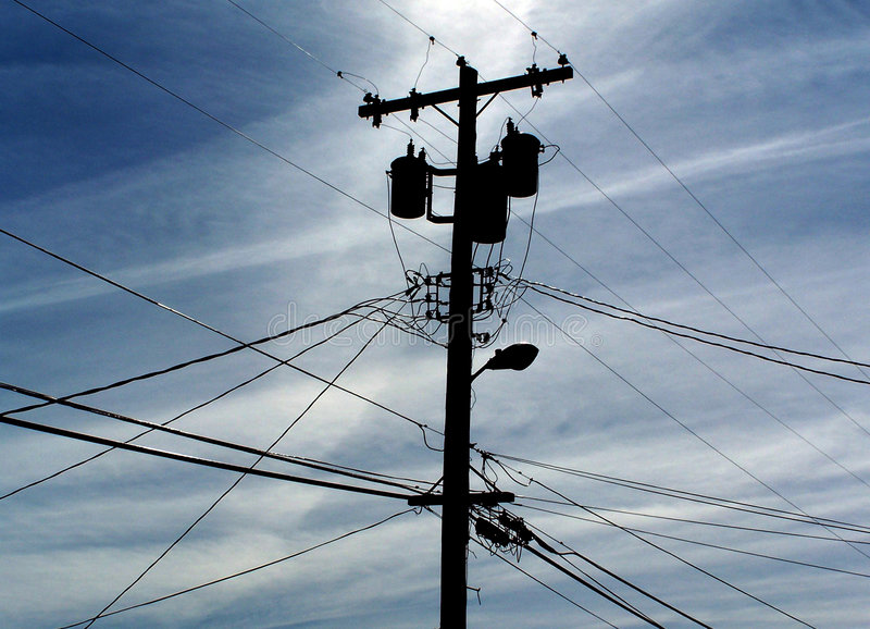 Telephone Pole. A telephone pole silhouetted against a blue sky stock photography