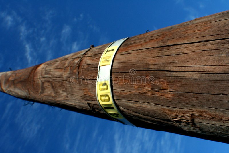 Telephone pole and blue sky. Telephone pole extending up into a blue sky stock photography