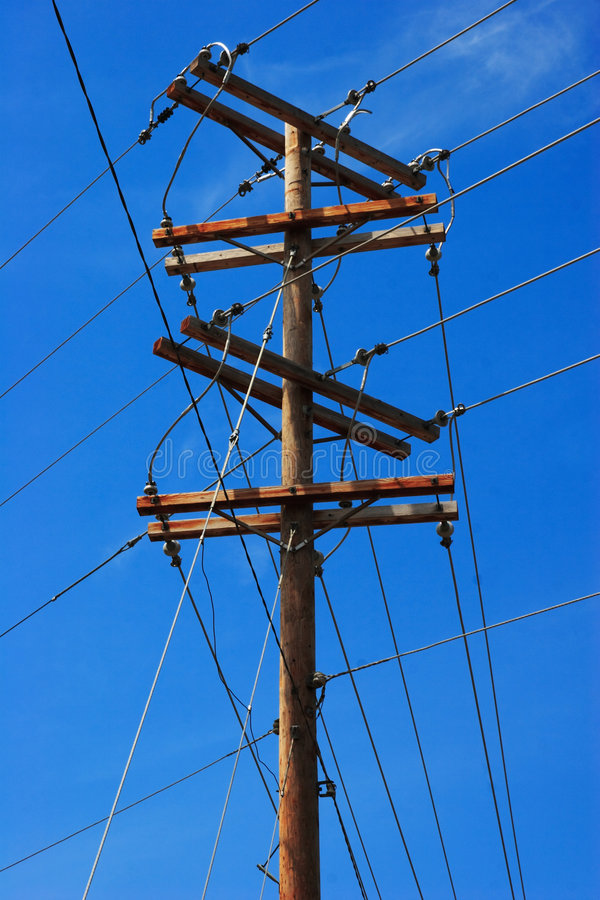 Telephone pole on blue sky. Telephone pole with wires and cables on a blue sky royalty free stock image