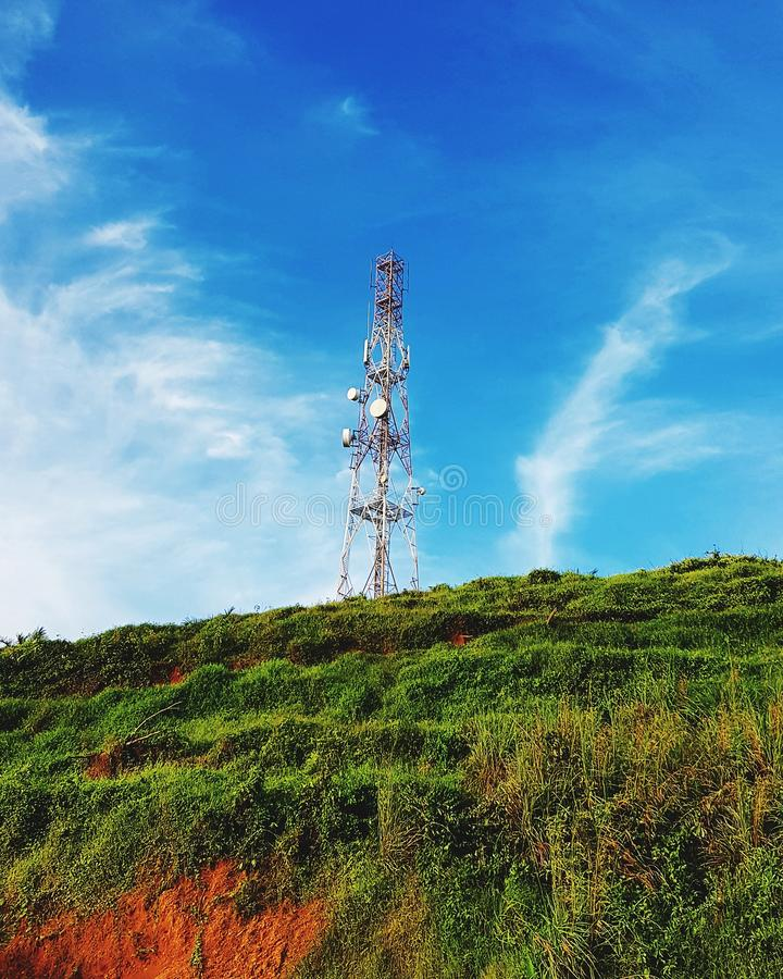 Telephone pole on hill against blue sky. Cellular, connection, radio, wireless, technology, telecommunication, electricity, tower stock photos