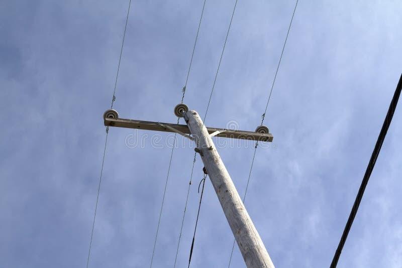 Telephone pole power line. A single telephone pole with power lines against a wispy cloudy blue sky stock image