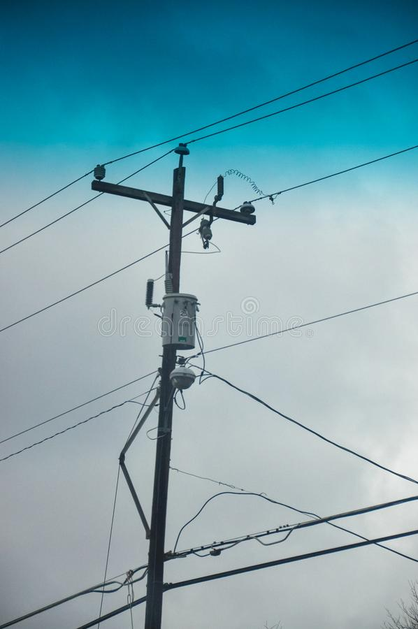 Telephone pole. A telephone pole silhouetted against a cloud sky before a coming rain royalty free stock images