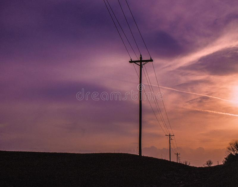 We march onward. Telephone poles in a line travel toward the horizon under a surreal, and frightening sky. The sun barely peeks through stock photography