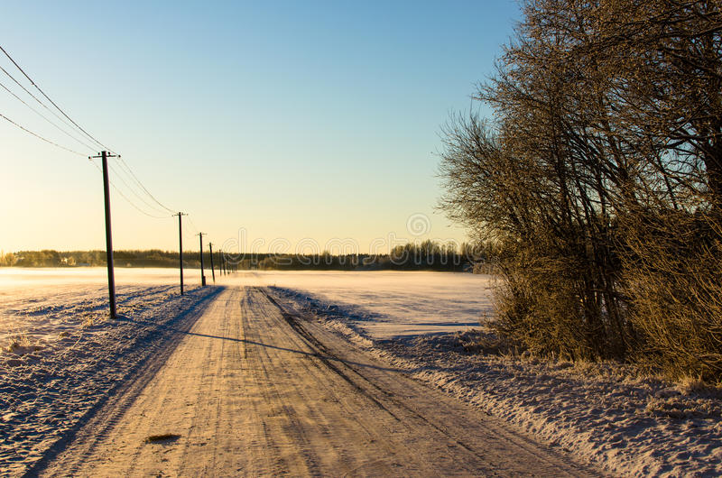 Telephone poles by a snowy countryside road. Blue skies above a white landscape in the Baltic winter at Lokuta in Turi, Estonia royalty free stock images