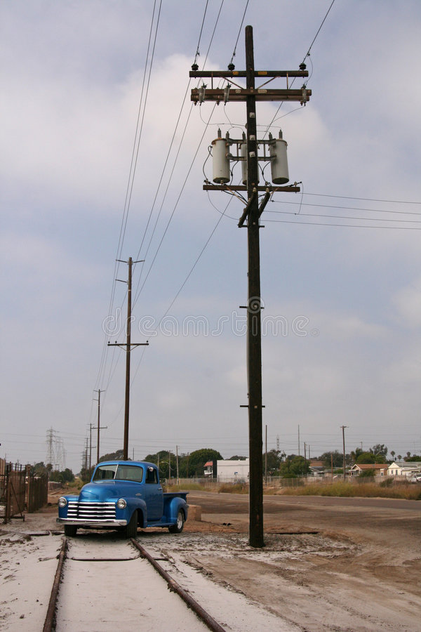 Telephone poles, train track, truck. Several telephone poles adjacent to a train track with a shiny blue 1953 truck parked on the track stock image