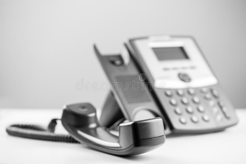Telephone receiver off the hook. Greyscale image of a telephone receiver off the hook to either effectively block the line or waiting for a person to arrive to stock photo