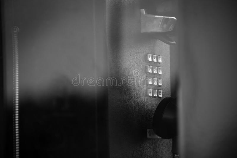 Telephone from a telephone booth in black and white. Close up images of a telephone from a telephone booth from the 1990`s. Space for copy royalty free stock photography