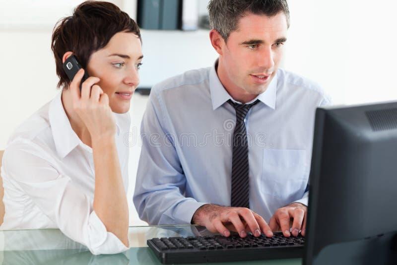 Telephonierende Frau während ihr Kollege lizenzfreies stockbild