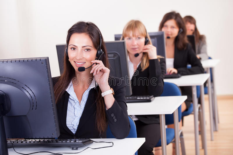 Telephonists in a call centre. Row of attractive young telephonists seated at computers wearing headsets and microphones in a call centre or client services help royalty free stock images