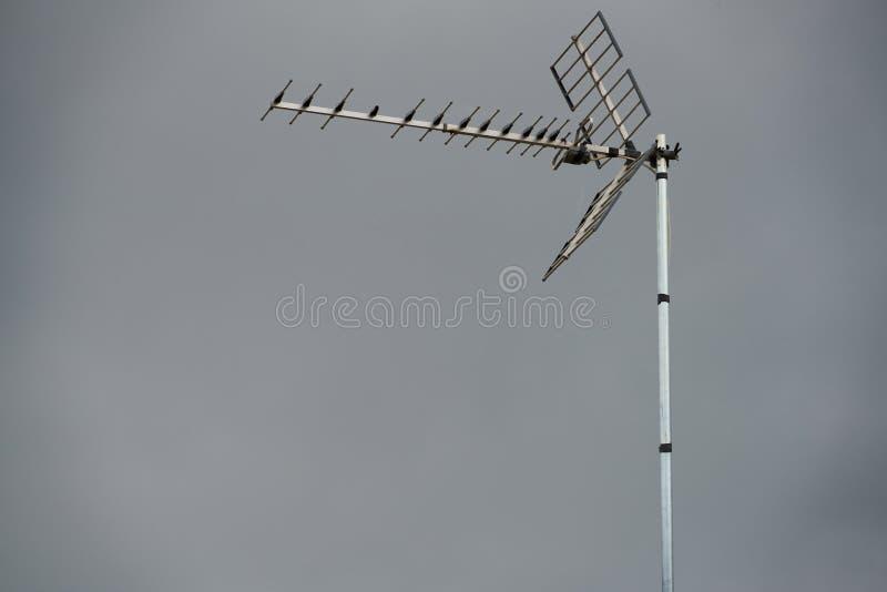 Telephoto obiektyw telewizyjna antena na dachu z popielatym nieba tłem fotografia stock