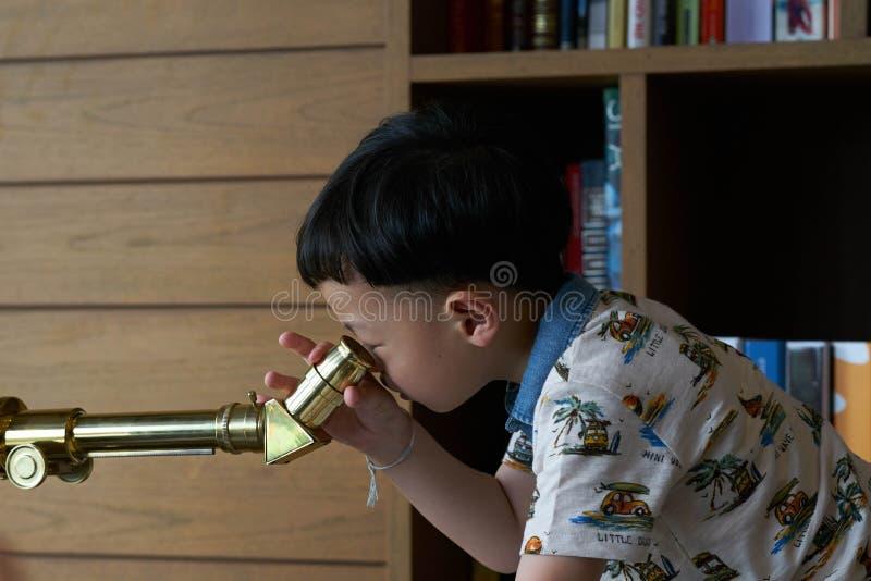 Telescópio do uso da criança ou do menino imagens de stock