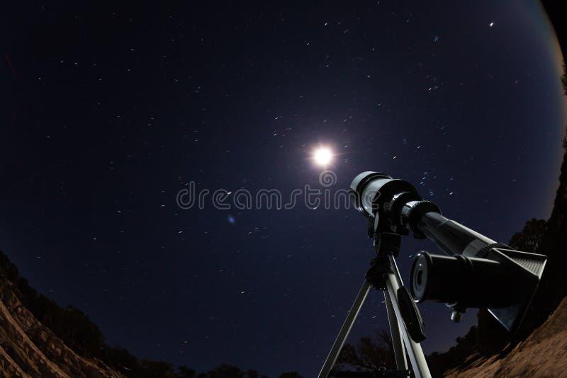Telescoop over nachthemel met sterren en maan stock foto's