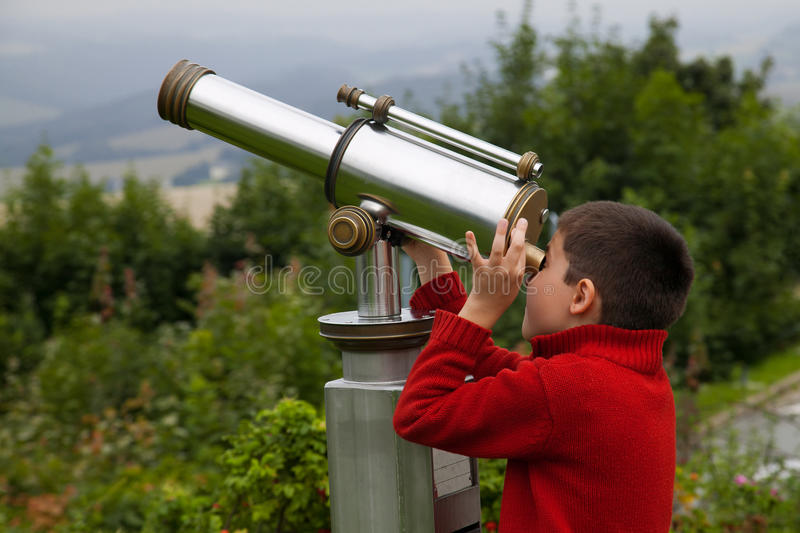 Telescope. Boy looking into the sky through a telescope royalty free stock photos