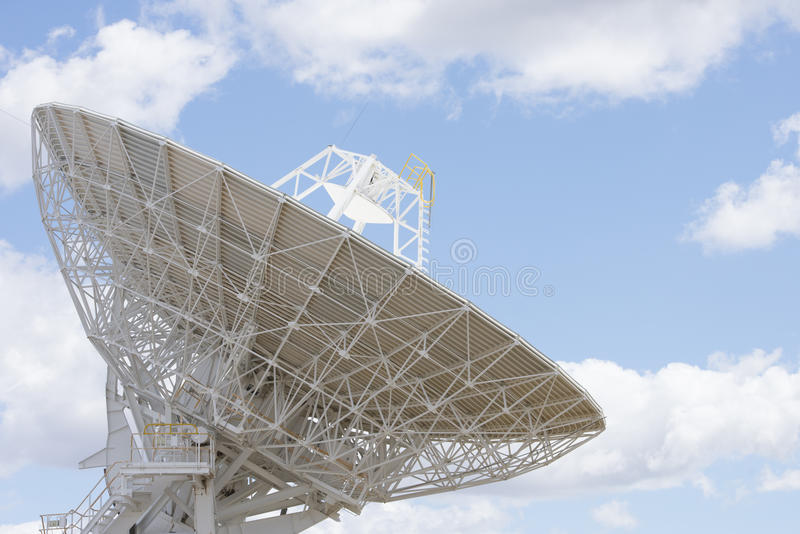 Telescope antenna dish with blue sky and clouds royalty free stock images