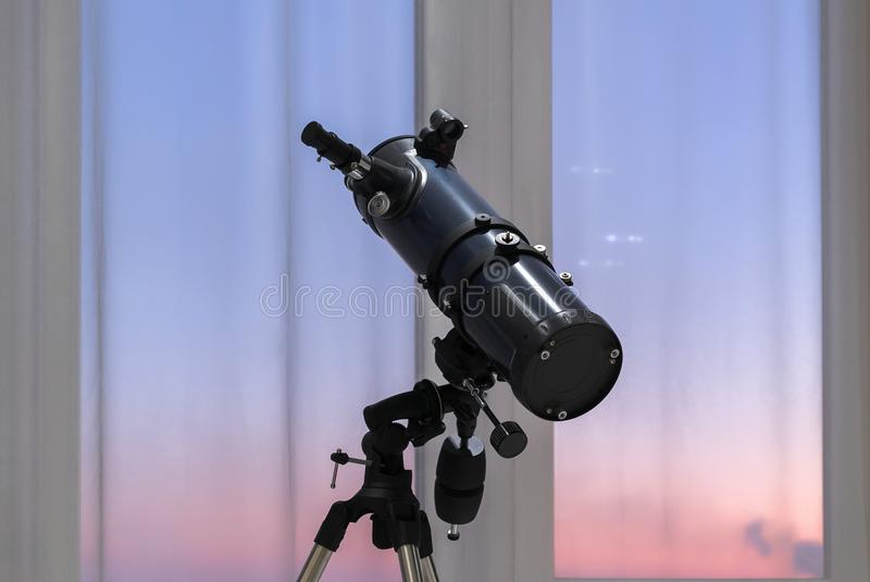 Telescope in the background of a window royalty free stock images