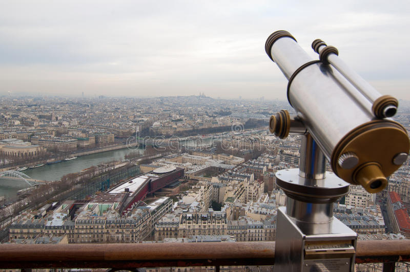 Telescope on Eiffel Tower in Paris, France. Aerial view of Paris and a telescope on Eiffel Tower on a cloudy day royalty free stock photography