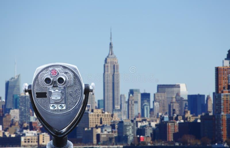 Manhattan skyline. Traditional silver telescope / binoculars overlooking Manhattan skyline, New York city in this travel concept stock image
