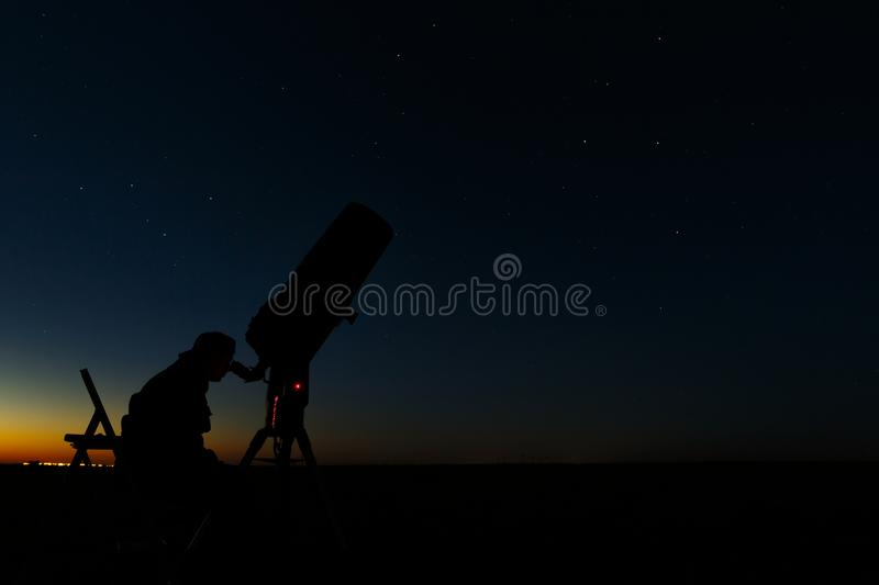 Telescope for the study of stars and planets. An astronomer makes observations in the open air.  stock photo