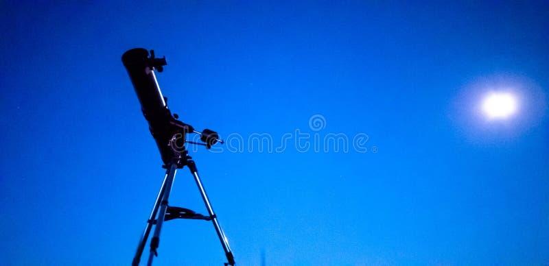 Telescopio en un trípode en la noche en naturaleza contra el contexto del cielo estrellado fotografía de archivo