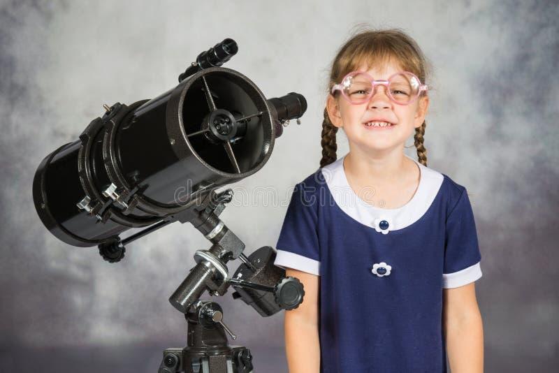 Telescopio que hace una pausa sonriente divertido del astrónomo aficionado con gafas de la muchacha imagen de archivo