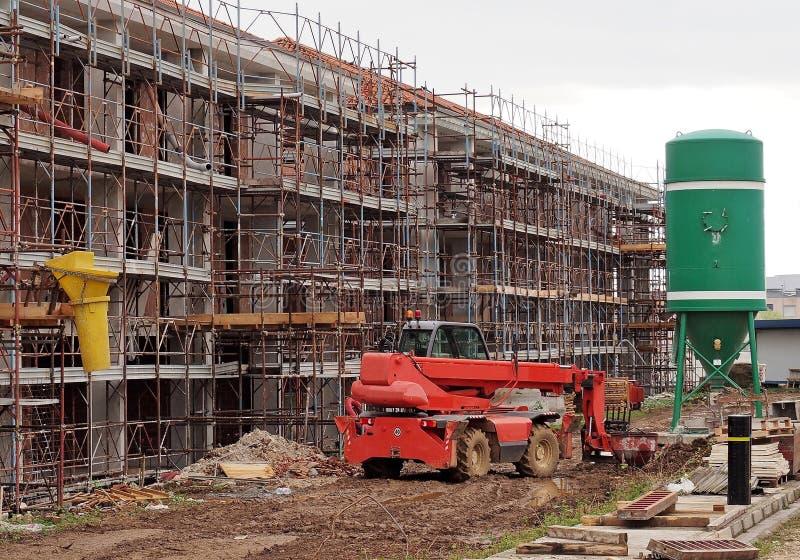 Telescopische manager tussen een gebouw die in aanbouw met steiger wordt behandeld en een concrete het groeperen silo royalty-vrije stock foto