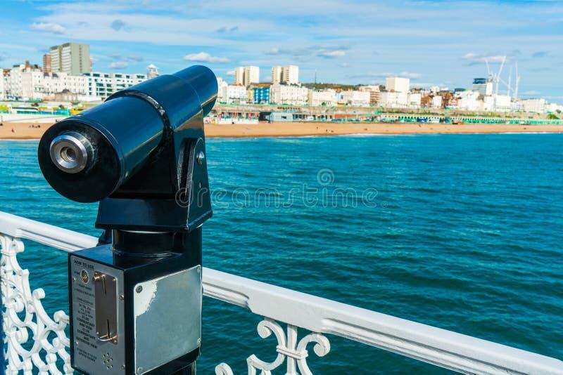Teleskop- eller kikaremynt för handelsresande, besökare eller turist på Brighton Pier med den Brighton Pier gränsmärket fotografering för bildbyråer
