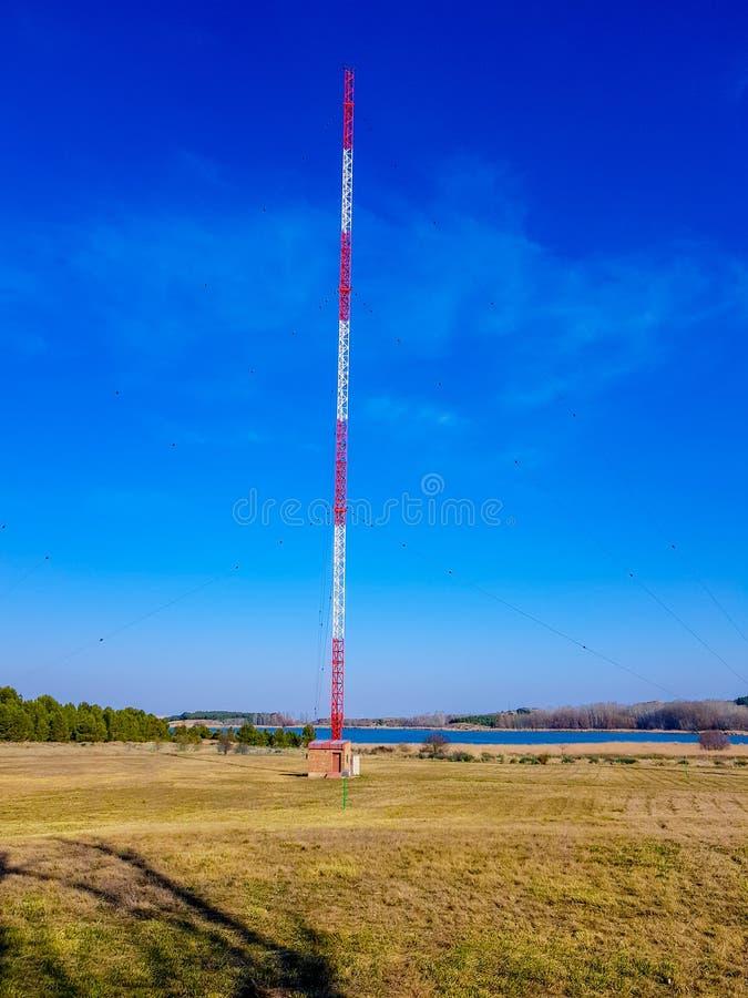 teletechniczny wierza blisko jeziora z niebieskiego nieba tłem fotografia stock