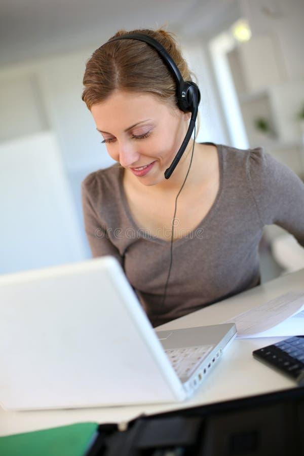 Teletrabajo de la mujer joven en el ordenador portátil con las auriculares imagen de archivo