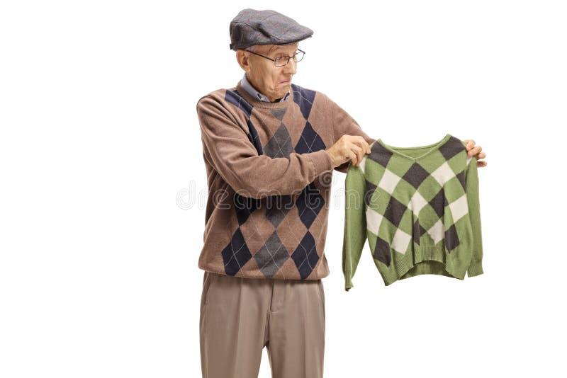 Teleurgesteld bejaarde die een gekrompen blouse bekijken royalty-vrije stock afbeelding