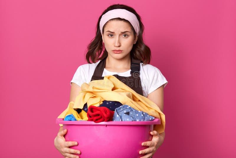 Teleurgesteld emotioneel wijfje met lichte hoofdband, witte t-shirt en bruine schort, die wasserij, uitgeput van huishoudenkarwei stock fotografie