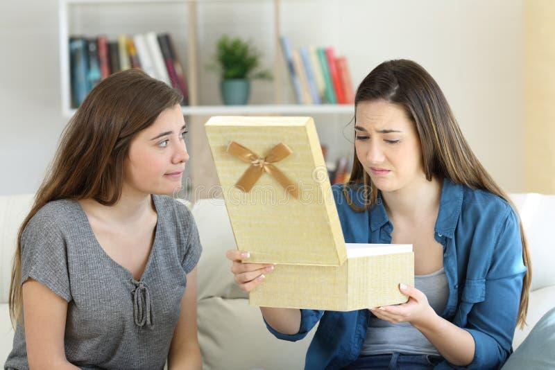 Teleurgesteld meisje die een gift naast haar vriend openen stock afbeelding