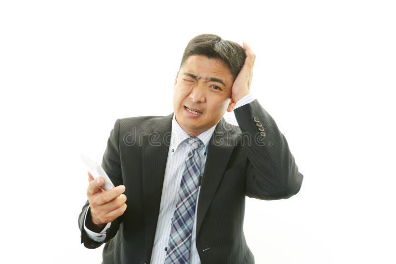 Teleurgestelde Aziatische zakenman stock afbeeldingen