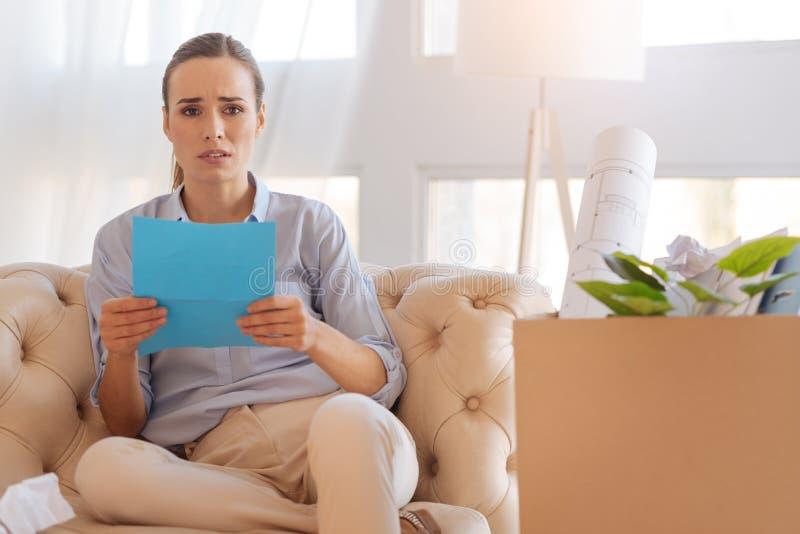 Teleurgestelde jonge vrouw die droevig terwijl het lezen van het document kijken stock afbeeldingen