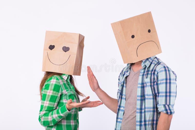 Teleurgestelde man die met zakken over hoofden zijn vrouw verwerpen royalty-vrije stock fotografie