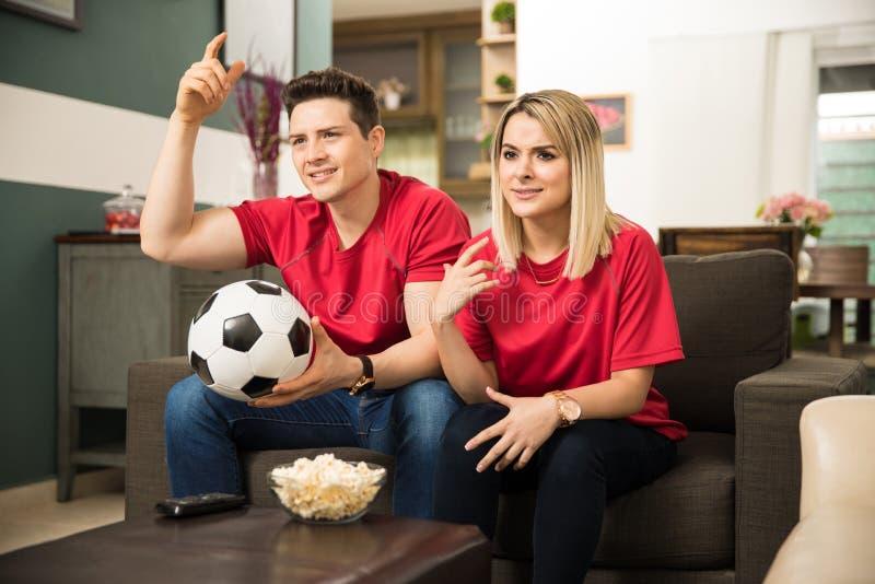Teleurgestelde voetbalventilators die op een spel letten stock afbeeldingen
