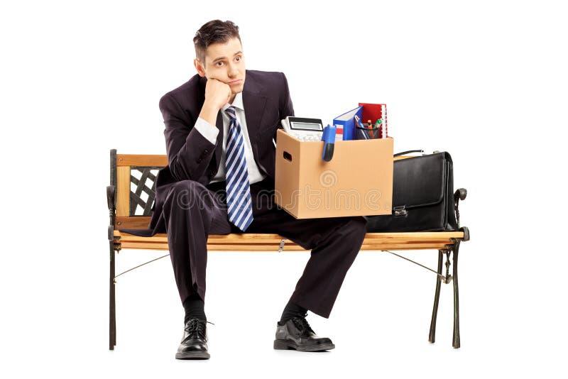 Teleurgestelde zakenman in een kostuumzitting op een bank met een doos stock foto