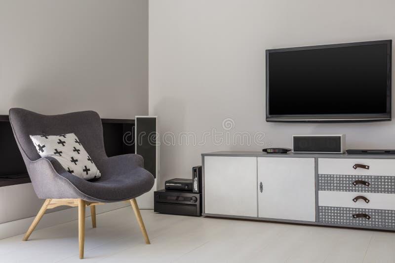 Televisão acima do armário ao lado da poltrona cinzenta com pi modelado imagem de stock
