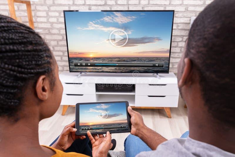 Televis?o de conex?o dos pares atrav?s do r?dio na tabuleta fotografia de stock royalty free