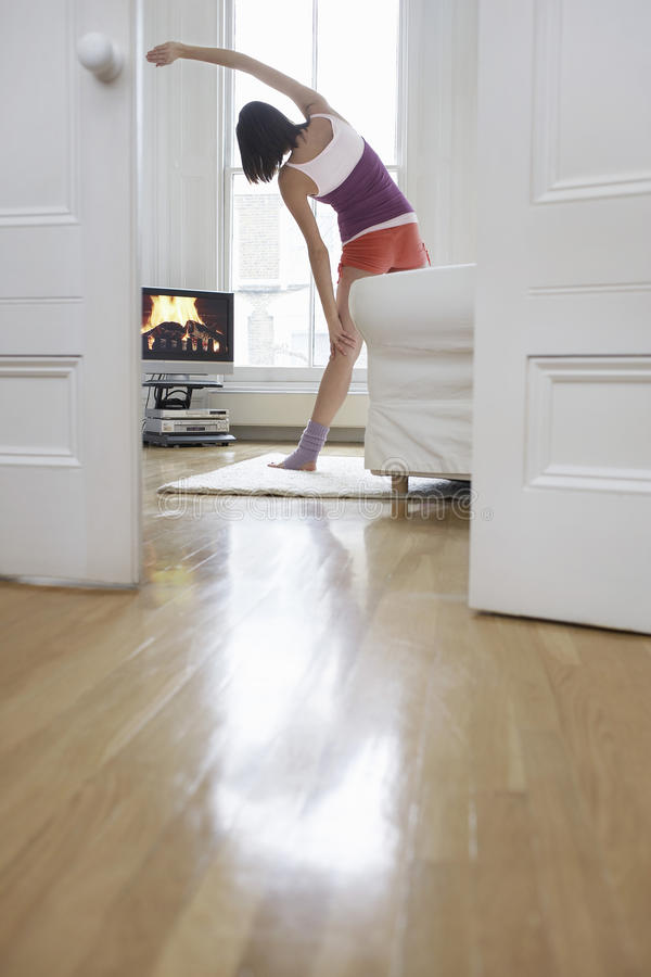 Televisão de exercício e de observação da mulher em casa imagem de stock royalty free